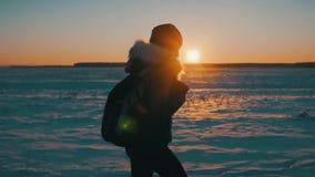 La silueta de un viajero feliz joven de la muchacha con una mochila va en la puesta del sol, viaje del invierno, forma de vida, c almacen de video