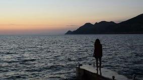 La silueta de una muchacha que salga en el muelle y mira el mar almacen de metraje de vídeo