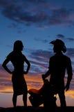 La silueta de una mujer en caderas apretadas de las manos del vestido mira al vaquero lateral Fotografía de archivo libre de regalías