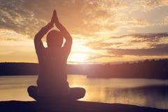 La silueta de la yoga de la mujer mayor cerca del lago durante puesta del sol, relaja tiempo y ejercicio Imágenes de archivo libres de regalías