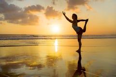 La silueta del ajuste de los jóvenes y la mujer atractiva del deporte en yoga de la puesta del sol de la playa practican el entre foto de archivo