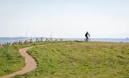 La silueta del ciclista en la bici del camino en el deporte del mediodía y el tiempo activo de la puesta del sol del concepto de  imagen de archivo