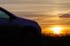 La silueta del coche en la puesta del sol Fotos de archivo libres de regalías