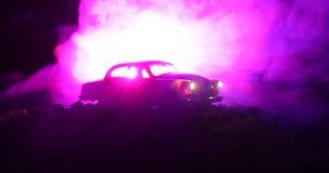 La silueta del coche viejo del vintage en fondo entonado de niebla oscuro con brillar intensamente se enciende en luz corta, o si