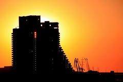 La silueta del edificio y del puerto cranes en la ciudad en la puesta del sol, Ucrania de Dnepr Foto de archivo