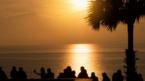 La silueta del grupo de gente joven, amigos, equipo que se coloca de goce junta ve el cielo anaranjado en la puesta del sol sobre Imagen de archivo libre de regalías