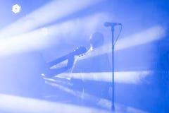 La silueta del guitarrista se realiza en una etapa del concierto Fondo musical abstracto Banda de la música con el guitarrista El imágenes de archivo libres de regalías