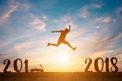 La silueta del hombre feliz salta entre 2017 y 2018 años en soles Foto de archivo libre de regalías
