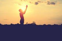 La silueta del hombre ruega con el fondo de la puesta del sol Imagen de archivo