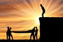 La silueta del hombre se prepone hacer un salto abajo, gente que el vnitsu le ayuda con seguridad a aterrizar foto de archivo libre de regalías