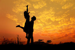 La silueta del hombre y la mujer aman en puesta del sol Imágenes de archivo libres de regalías