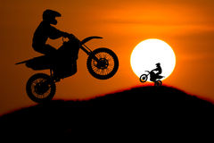 La silueta del jinete de la moto salta la cuesta cruzada de la montaña con Foto de archivo