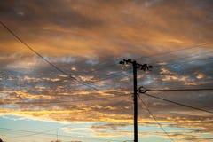 La silueta del las líneas eléctricas en la parte posterior de Ridge del relámpago se encendió por una puesta del sol foto de archivo