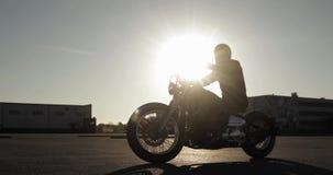 La silueta del motorista del hombre en la motocicleta está montando en el camino en ciudad en la puesta del sol almacen de metraje de vídeo