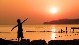 La silueta del niño contra la puesta del sol anaranjada Foto de archivo