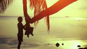 La silueta del padre feliz joven juega con su hija en la palmera contra la perspectiva de la puesta del sol hermosa del mar almacen de metraje de vídeo