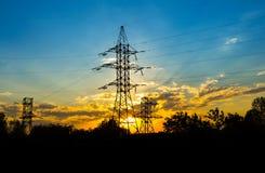 La silueta del pilón de la transmisión de la electricidad de la tarde Imagenes de archivo