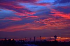 La silueta del poste eléctrico y la grúa se elevan en cielo de la salida del sol Imágenes de archivo libres de regalías