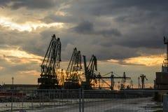 La silueta del puerto cranes contra un cielo dramático en la puesta del sol fotografía de archivo libre de regalías