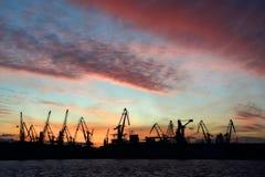 La silueta del puerto cranes en fondo del cielo de la puesta del sol fotografía de archivo libre de regalías