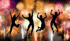 La silueta del salto del muchacho y de la muchacha feliz goza brillantemente de los fuegos artificiales coloridos Imagenes de archivo