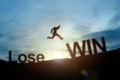 La silueta del salto que brilla intensamente del hombre de negocios pierde para ganar éxito concentrado imagenes de archivo
