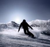 La silueta del Snowboarder va abajo por la cuesta del esquí de la alta montaña Imagen de archivo libre de regalías