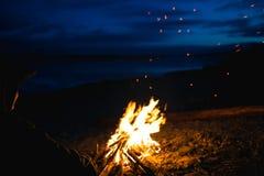 La silueta del turista de la muchacha alrededor de la hoguera en la noche en la orilla del río imagen de archivo