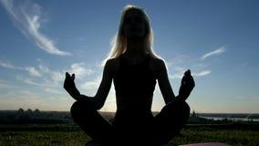 La silueta delgada hermosa joven de la mujer practica yoga en la playa en la puesta del sol Yoga en la salida del sol metrajes