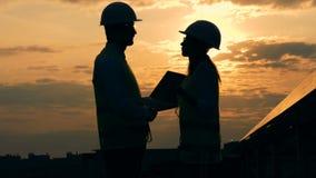 La silueta dos de ingenieros está teniendo una conversación sobre un tejado durante puesta del sol metrajes