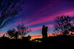 La silueta junta la abrazo del hombre y de la mujer con feliz entre el cielo hermoso de la puesta del sol en naturaleza imagen de archivo