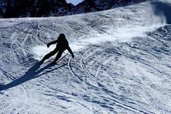 La silueta retroiluminada del hombre en el esquí practicante de la acción que va rápido y agresivo abajo nieva deporte de inviern Foto de archivo libre de regalías