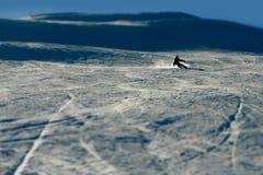 La silueta retroiluminada del hombre en el esquí practicante de la acción que va rápido y agresivo abajo nieva deporte de inviern Imagenes de archivo