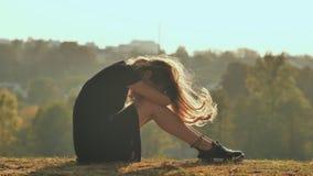 La silueta triste de la muchacha se sienta solamente en la hierba tan sola y el grito almacen de video