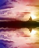 La silueta triste del muchacho se preocupó en el prado en la puesta del sol con agua con referencia a Fotografía de archivo