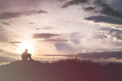 La silueta triste del muchacho se preocupó en el prado en la puesta del sol, silueta c Fotografía de archivo libre de regalías