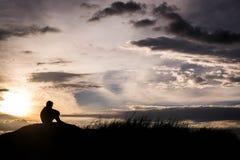 La silueta triste del muchacho se preocupó en el prado en la puesta del sol, silueta c Fotografía de archivo