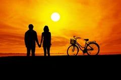 La siluetta degli amanti e della bici durante il tramonto immagini stock
