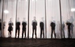 La siluetta degli uomini dietro la tenda nel teatro in scena, l'ombra dietro le scene è simile al bianco e al bla fotografia stock