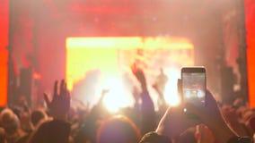 La siluetta dei fan e del telefono cellulare di salto fa le video scene in unfocused alla notte stock footage