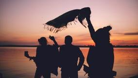 La siluetta dei giovani di dancing del gruppo ha un partito alla spiaggia sul tramonto fotografia stock