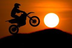 La siluetta del cavaliere della motocicletta salta la pendenza trasversale della montagna con Fotografia Stock Libera da Diritti
