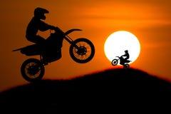 La siluetta del cavaliere della motocicletta salta la pendenza trasversale della montagna con Fotografia Stock