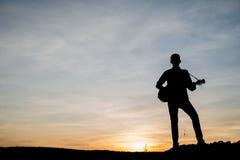 La siluetta del giocatore di chitarra salta sulla pietra Fotografia Stock Libera da Diritti