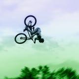 La siluetta del giovane non identificato esegue le acrobazie su fondo del cielo vivo Sport e rischio di Extrem fotografie stock libere da diritti