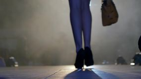 La siluetta del modello snello nelle scarpe alla moda va lungo la passerella in fumo alla sfilata di moda archivi video