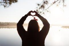 La siluetta del ` s della donna passa la formazione della forma del cuore sull'alba di mattina Fotografie Stock Libere da Diritti