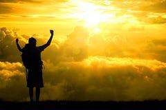 La siluetta del viaggiatore con zaino e sacco a pelo degli uomini a braccia aperte si è alzata verso sul cielo di speranza ad eff immagini stock libere da diritti