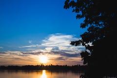 La siluetta dell'albero sulla destra con il fiume ed il sole si svasano sul tramonto Immagine Stock