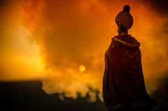 La siluetta dell'uomo arabo sta da solo nel deserto e nella sorveglianza del tramonto con le nuvole di nebbia Favola orientale Immagini Stock